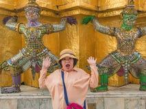 Портрет старших азиатских женщин делает сюрпризом с гигантским подъемом пагоду в виске Бангкоке Таиланде Wat Phrakaew стоковое фото