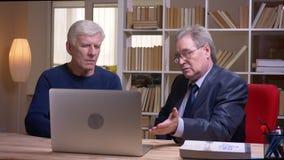 Портрет старших бизнесменов сидя совместно на таблице наблюдая в ноутбук и обсуждая серьезно проект сток-видео