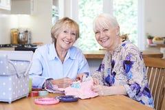 Портрет 2 старших женщин шить лоскутное одеяло совместно Стоковые Фотографии RF