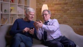 Портрет старших мужских друзей показывая смартфоны друг к другу и смеясь joyfully видеоматериал
