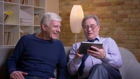 Портрет старших мужских друзей сидя совместно на софе быстро проводя пальцем по фото на планшете для того чтобы сделать решение акции видеоматериалы