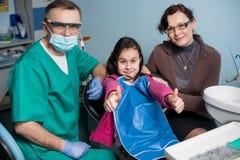 Портрет старших педиатрических дантиста и девушки с ее матерью на первом зубоврачебном посещении на зубоврачебном офисе стоковое фото rf