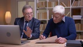 Портрет старых бизнесменов работая вместе с ноутбуком и бумагами обсуждая серьезно будущий проект сток-видео