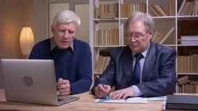Портрет старых бизнесменов работая вместе с ноутбуком и бумагами обсуждая активно будущий общий проект акции видеоматериалы