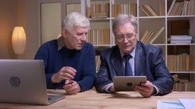 Портрет старых бизнесменов работая вместе с ноутбуком и планшетом обсуждая серьезно проект видеоматериал