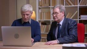 Портрет старых бизнесменов сидя совместно на таблице работая с ноутбуком и обсуждая активно проект акции видеоматериалы