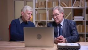 Портрет старых бизнесменов сидя совместно на таблице работая с ноутбуком и обсуждая серьезно проект видеоматериал