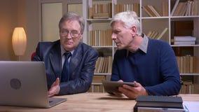Портрет старых бизнесменов сотрудничая с ноутбуком и планшетом обсуждая серьезно будущий проект сток-видео