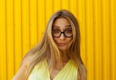 Портрет стекел игрушки радостной девушки нося смешных над желтым цветом Стоковое Изображение