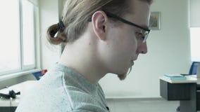 Портрет стекел программиста нося и кабеля, который был busted на работе Он падает его голова вниз Камера от видеоматериал