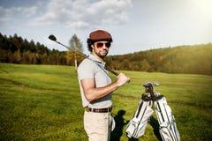 Портрет стильного игрока в гольф в стеклах стоя на wi поля для гольфа стоковое фото