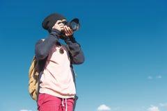 Портрет стильного хиппи девушки в шляпе и с рюкзаком который фотографирует она на камере DSLR outdoors Стоковая Фотография