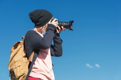 Портрет стильного хиппи девушки в шляпе и с рюкзаком который фотографирует она на камере DSLR outdoors Стоковое Фото