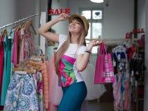 Портрет стильной дамы с хозяйственными сумками в ее руках в магазине одежды женщина ног принципиальной схемы мешка предпосылки хо Стоковое Изображение RF