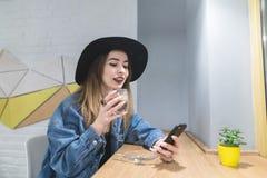 Портрет стильной и положительной девушки с smarthon в ее руках выпивая горячее питье в уютном кафе Стоковые Фото