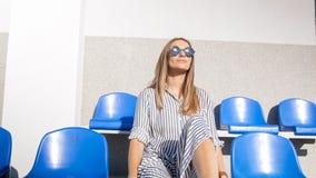 Портрет стильной молодой женщины в солнечных очках сидя на пустом стадионе Стоковые Изображения