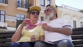 Портрет стильных старых людей выпивает кофе и ослаблять на стенде в городе акции видеоматериалы
