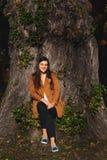 Портрет стиля молодой женщины городского, сидя в парке сезон путя пущи падения осени стоковое изображение