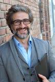 Портрет стильного бизнесмена с стеклами усмехаясь вне офиса Стоковые Изображения RF