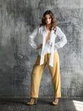 Портрет стильной молодой женщины в белой рубашке и желтых брюках стоковое изображение