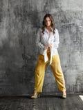 Портрет стильной молодой женщины в белой рубашке и желтых брюках стоковая фотография rf