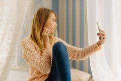 Портрет стороны конца-вверх белокурого девочка-подростка принимая selfie через мобильный телефон Стоковая Фотография RF