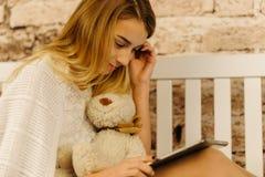 Портрет стороны конца-вверх девушки используя таблетку пока держащ плюшевый медвежонка Стоковое Изображение RF