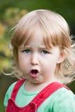 Портрет стороны крупного плана жевать милые 2 лет старой белокурой белой девушки на предпосылке лета на открытом воздухе стоковое изображение