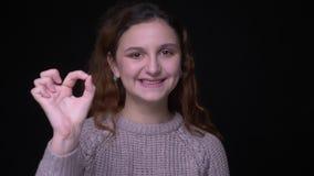 Портрет студента милого молодого брюнета волнист-с волосами делает в порядке знак показать все хорошее на черной предпосылке видеоматериал