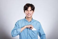 Портрет студии азиатского человека держа карточку Стоковая Фотография RF