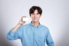 Портрет студии азиатского человека держа карточку Стоковые Изображения RF
