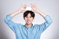 Портрет студии азиатского человека держа карточку Стоковое Изображение RF