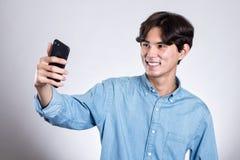 Портрет студии красивого азиатского человека держа умный телефон Стоковые Изображения