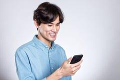 Портрет студии красивого азиатского человека держа умный телефон Стоковые Фотографии RF