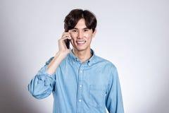Портрет студии красивого азиатского человека держа умный телефон Стоковое фото RF
