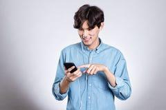 Портрет студии красивого азиатского человека держа умный телефон Стоковое Изображение RF