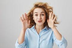 Портрет студии красивой смешной женщины с ладонями повышения вьющиеся волосы приближает к стороне и усмехаться если развлекающ не стоковая фотография
