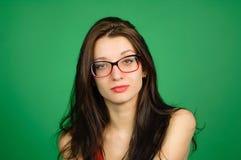 Портрет студии милой умной девушки в Eyeglasses и красном верхе на зеленой предпосылке Стоковое Изображение