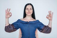 Портрет студии очаровательной положительной кавказской женской коммерсантки пробуя ослабить пока размышляющ, стоя с поднятыми рук стоковая фотография