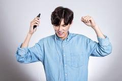 Портрет студии радостного азиатского человека с умным телефоном и музыкой Стоковые Изображения