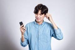 Портрет студии радостного азиатского человека с умным телефоном и музыкой Стоковое фото RF