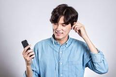 Портрет студии радостного азиатского человека с умным телефоном и музыкой Стоковое Изображение RF