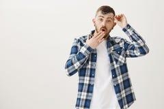 Портрет студии сотрясенного потревоженного привлекательного человека с бородой, принимая стекла и держа eyewear около лба стоковое фото