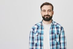 Портрет студии талии-вверх бородатого европейского мужчины смотря утомленный и усмехаясь уныло на камере, над серой предпосылкой стоковое изображение rf