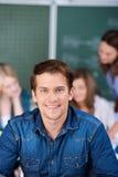 Портрет студента усмехаясь в классе стоковое изображение