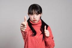 Портрет студии женщины двадчадк азиатской при удивленный взгляд держа большие пальцы руки вверх Стоковые Изображения