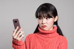 Портрет студии женщин двадчадк азиатских надоел телефоном стоковая фотография