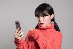 Портрет студии женщин двадчадк азиатских надоел телефоном стоковые фотографии rf