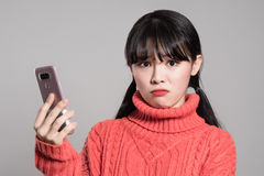 Портрет студии женщин двадчадк азиатских надоел телефоном стоковые изображения rf