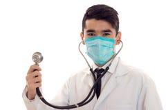Портрет студии мужского доктора в форме и маске при стетоскоп в его представлять рук изолированный на белой предпосылке Стоковое Изображение